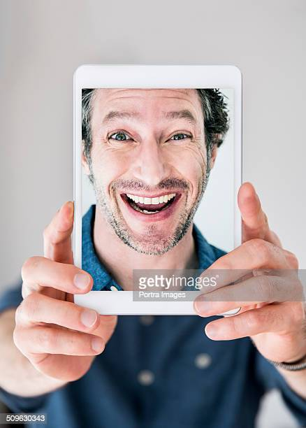 Playful man making faces while photographing self
