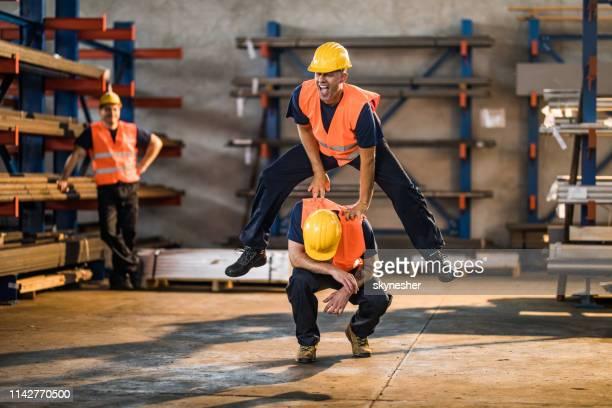 spielende handwerker spielen auf einer pause in einem lager. - handwerker stock-fotos und bilder