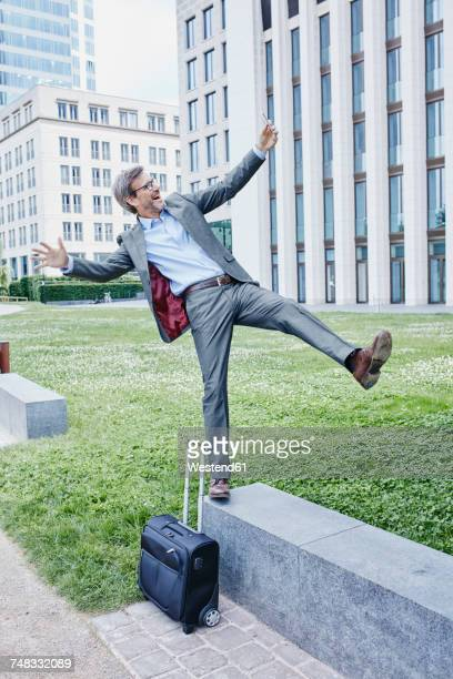 playful mature businessman with rolling suitcase balancing on wall taking a selfie - standing on one leg stock pictures, royalty-free photos & images
