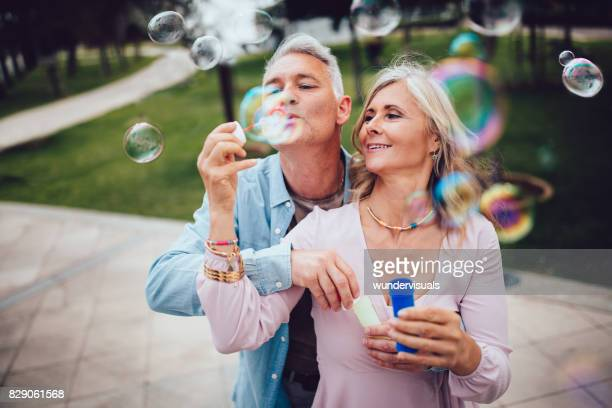 Playful mature couple blowing bubbles at the park