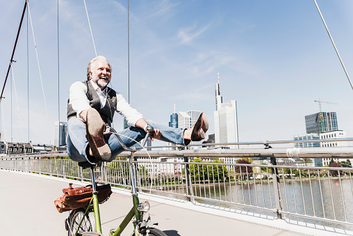 Playful mature man on bicycle on bridge in the city - gettyimageskorea