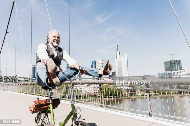 playful mature man on bicycle on bridge in the city - gleichgewicht stock-fotos und bilder