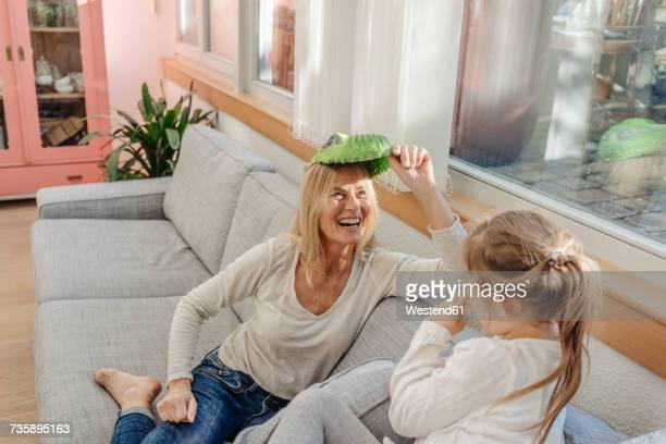 playful mature woman and girl at home on couch - mamie humour photos et images de collection
