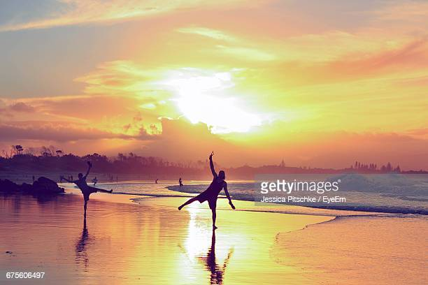 Playful Men At Beach Against Sky During Sunset