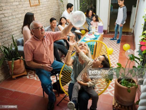 遊び心のあるメキシコの祖父母と孫が風船で遊んで