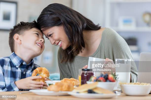 Playful mom enjoys breakfast at home with her son