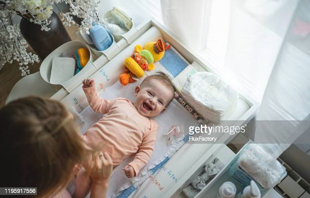 playful mother and a cheerful newborn daughter in home nursery - baby changing mat stock pictures, royalty-free photos & images