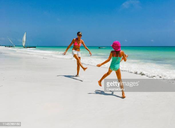 playful mother and daughter enjoying on tropical sandy beach - zanzibar island stock photos and pictures