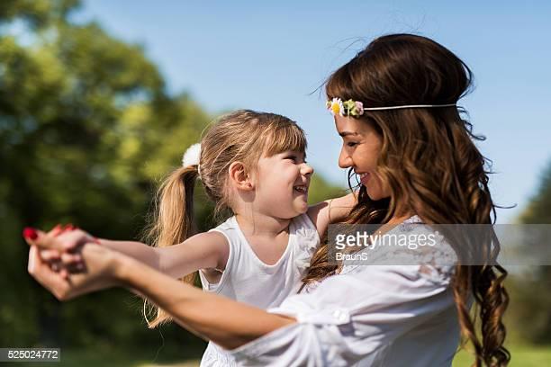Brincalhão mãe e filha a divertir-se juntos na natureza.