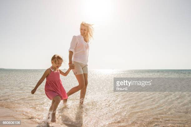 Playful mother and daughter running through sea.