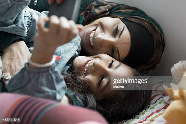 Playful mother and daughter using mobile phone in bedroom