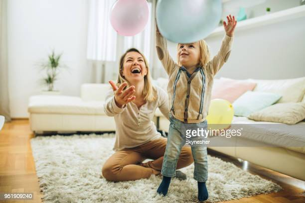 playful mother and son having fun with balloons in the living room. - nanny stock photos and pictures
