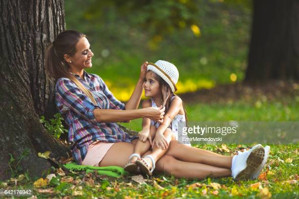 Playful mother having fun with her little girl outdoors.