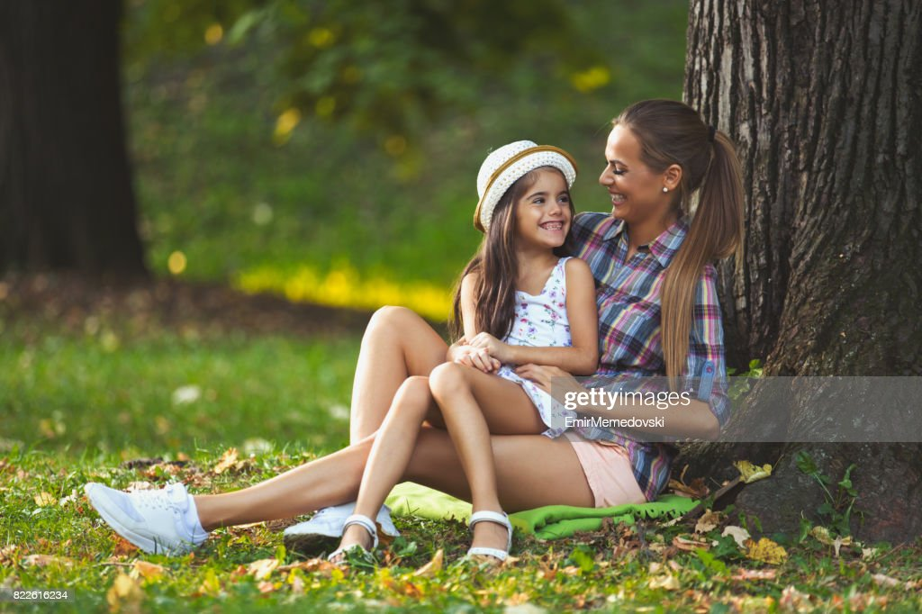 Playful mother having fun with her little girl outdoors. : Stock Photo