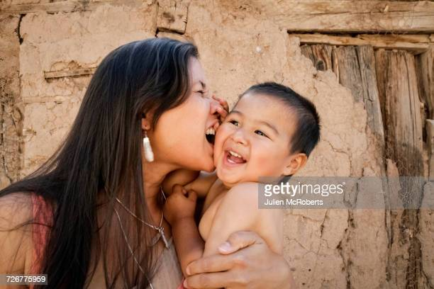 Playful mother holding son outdoors