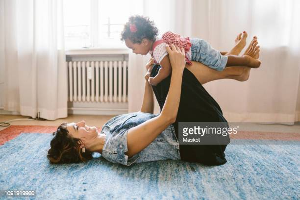playful mother lifting daughter while lying on carpet at home - 暖房用ラジエーター ストックフォトと画像