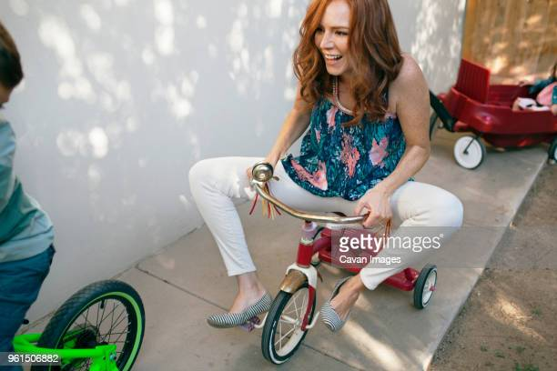playful mother riding tricycle with boy at backyard - tricycle stock pictures, royalty-free photos & images