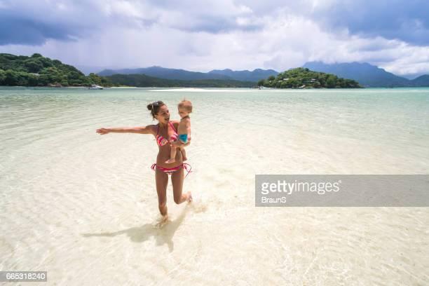 mère ludique courir avec son fils à travers la mer. - seychelles photos et images de collection