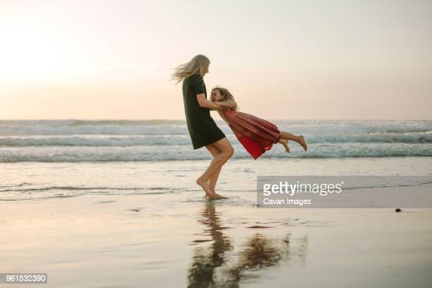 playful mother spinning daughter against sky at beach - swinging stock pictures, royalty-free photos & images