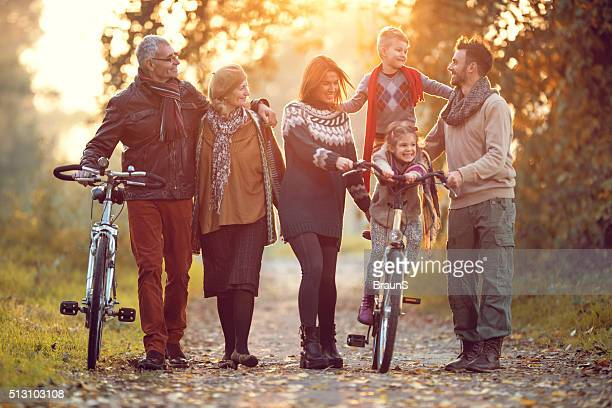 Playful multi-generation family having fun with bikes in nature.