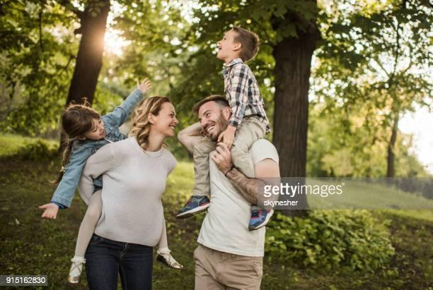 Les parents ludiques et leurs deux petits enfants s'amuser à l'extérieur au printemps.
