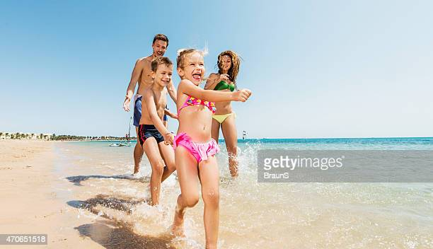 Verspielte Eltern verfolgen, die ihre Kinder am Strand.