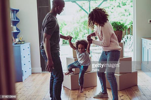 playful parents holding son's hands in new house - african american family home stock photos and pictures