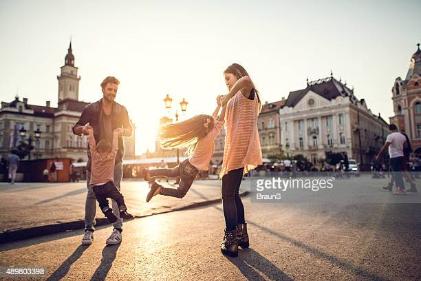Playful parents spinning their children in the city at sunset.