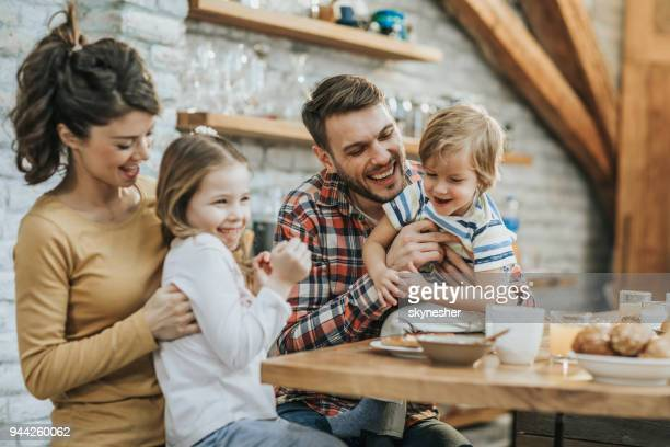 playful parents tickling their small kids in the kitchen. - famiglia con due figli foto e immagini stock