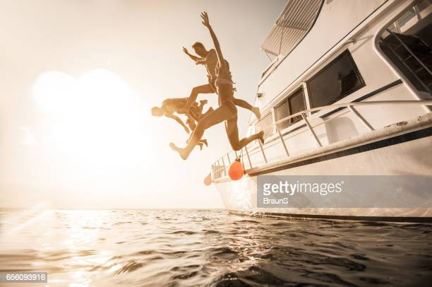 Playful people jumping from the boat into the sea.