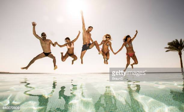 Playful people jumping together into the swimming pool.