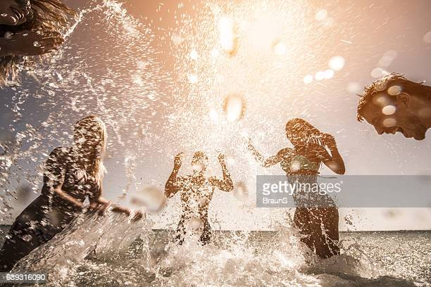 Playful people splashing each other in the sea.