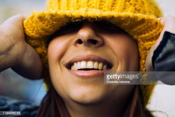 playful portrait of a young woman wearing a beanie - yellow hat stock pictures, royalty-free photos & images