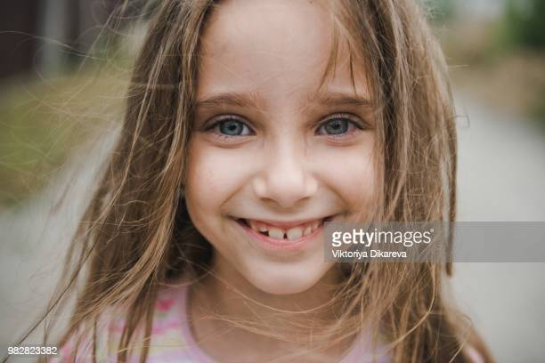 Playful portrait of cute little girl in the nature