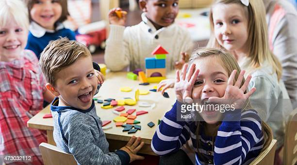 playful preschoolers having fun making faces - preschool building stock pictures, royalty-free photos & images