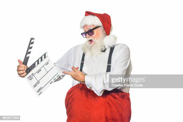 Playful Santa Claus pointing and looking a film slate with a celebration attitude wearing sunglasses and a white shirt with suspenders