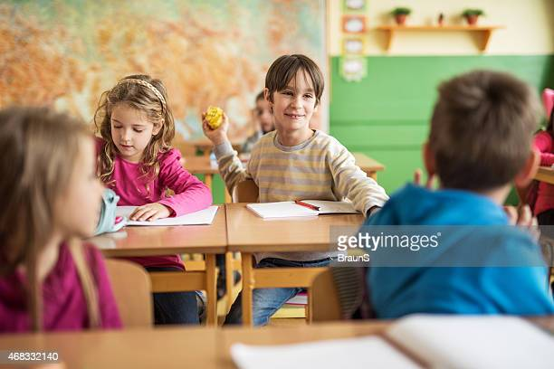Playful school children having fun in the classroom.