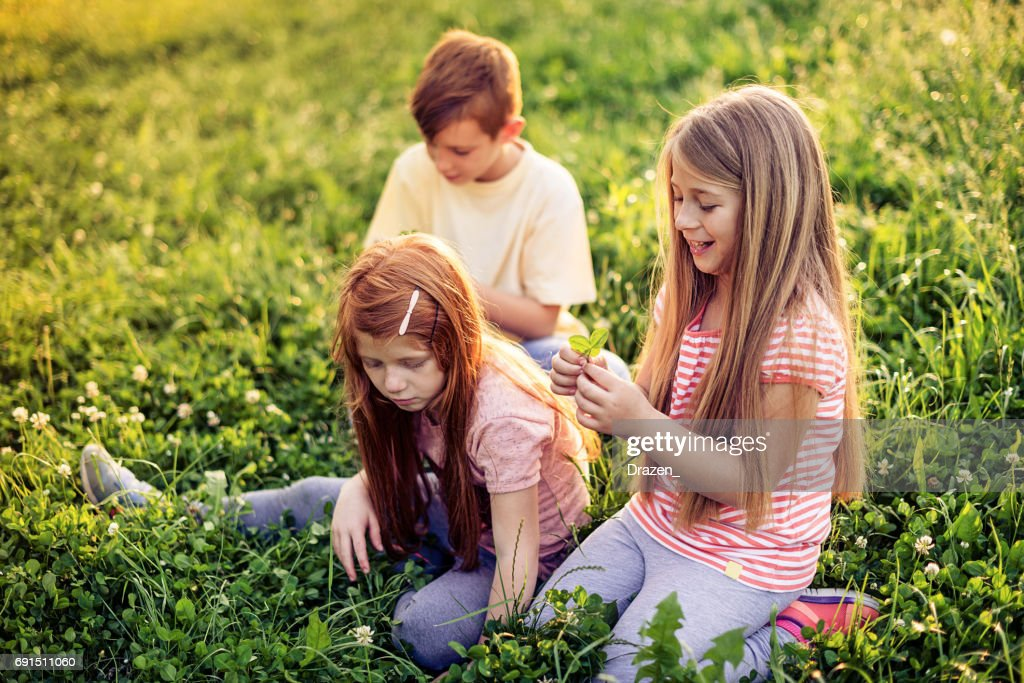 Playful school kids looking for four leaf clover in park : Stock Photo