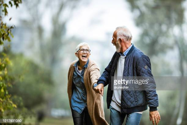 playful senior couple having fun in the park. - retirement stock pictures, royalty-free photos & images