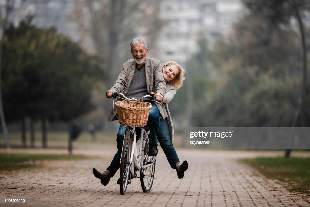 Verspieltes Seniorenpaar, das sich am Herbsttag auf dem Fahrrad amüst. : Stock-Foto