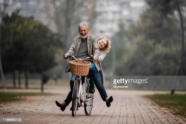 coppia senior giocosa che si diverte in bicicletta nella giornata autunnale. - coppia anziana foto e immagini stock