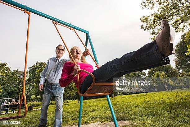 Playful senior couple having fun together while swinging on playground.