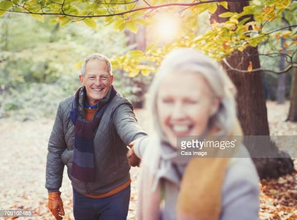 Playful senior couple holding hands in autumn park