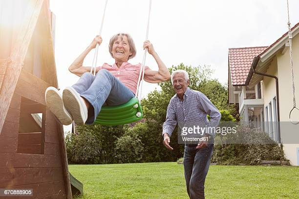 playful senior couple with swing in garden - swinging stock pictures, royalty-free photos & images