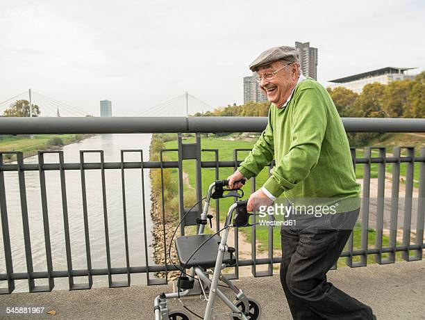 Playful senior man with wheeled walker on bridge