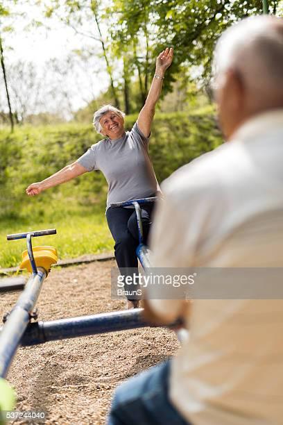 Playful senior woman having fun on seesaw at the playground.