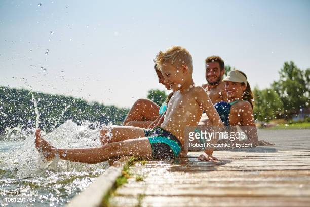 playful siblings sitting on pier with parents over lake during sunny day - vacanze foto e immagini stock