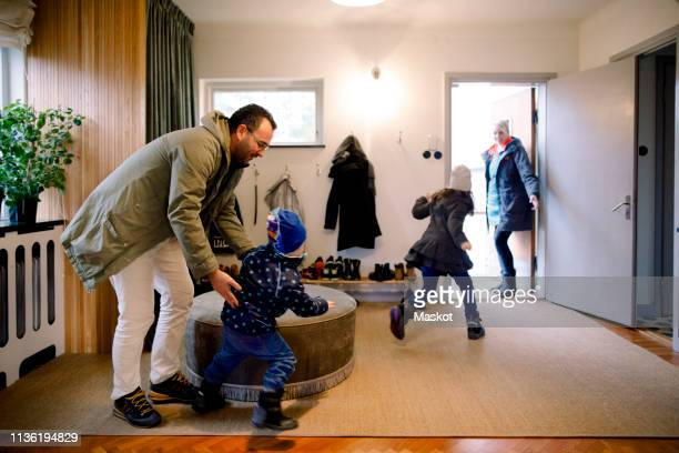 playful siblings with parents in mudroom at home - leaving stockfoto's en -beelden