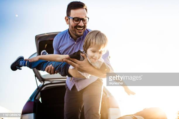 playful single father having fun with his small boy on the street. - family with one child stock pictures, royalty-free photos & images