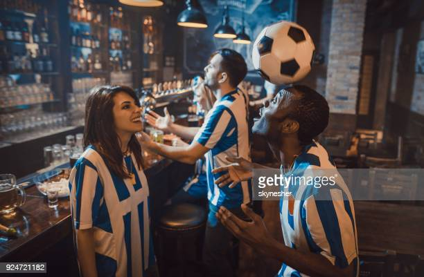 Playful soccer fans playing with ball on a half-time in a bar.
